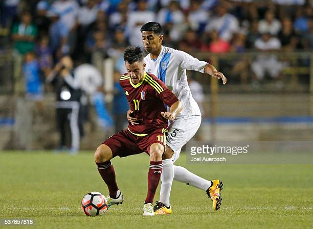 Moises Hernandez of Guatemala grabs Juan Pablo Anor of Venezuela as he attempts to take the ball away during first half action on June 1 2016 at...