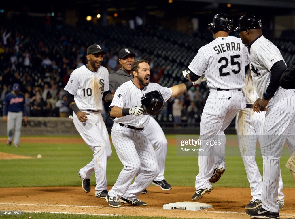 Moises Sierra #25 of the Chicago White Sox makes sure he touched first base as he celebrates with teammates Alexei Ramirez #10 and Adam Eaton #1 (C) after hitting a game-winning RBI single scoring Leury Garcia during the ninth inning against the Cleveland Indians at U.S. Cellular Field on May 28, 2014 in Chicago, Illinois. The White Sox defeated the Indians 3-2.