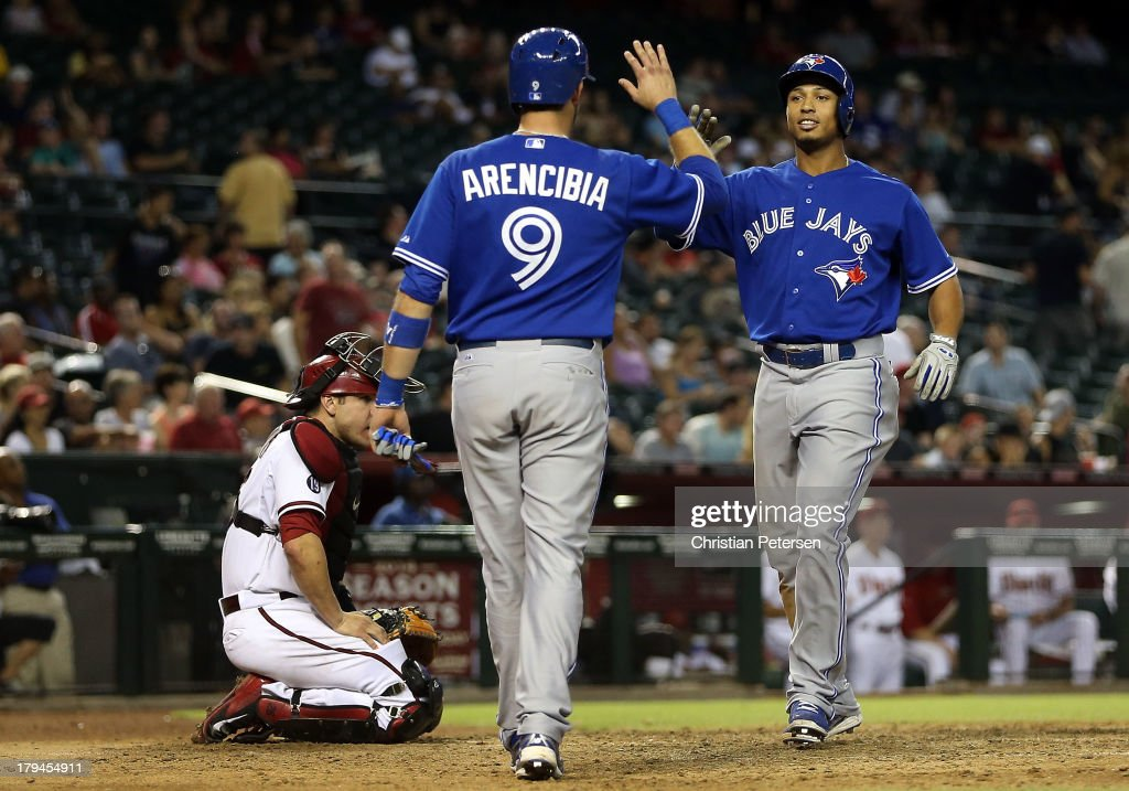 <a gi-track='captionPersonalityLinkClicked' href=/galleries/search?phrase=Moises+Sierra&family=editorial&specificpeople=7509137 ng-click='$event.stopPropagation()'>Moises Sierra</a> #14 of the Toronto Blue Jays high-fives <a gi-track='captionPersonalityLinkClicked' href=/galleries/search?phrase=J.P.+Arencibia&family=editorial&specificpeople=4959430 ng-click='$event.stopPropagation()'>J.P. Arencibia</a> #9 after hitting a two-run home run against the Arizona Diamondbacks during the ninth inning of the interleague MLB game at Chase Field on September 3, 2013 in Phoenix, Arizona.