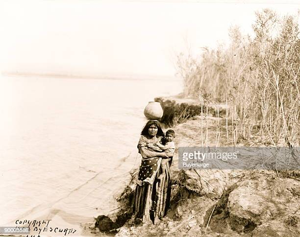 Mojave woman carrying water on her head and holding child