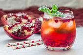 Mojito cocktail with pomegranate, mint, lemon juice and ice in glass, horizontal