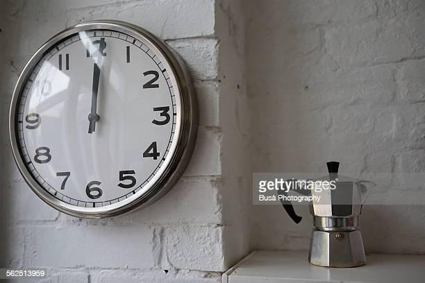 Moka coffee maker and a wall clock signing noon