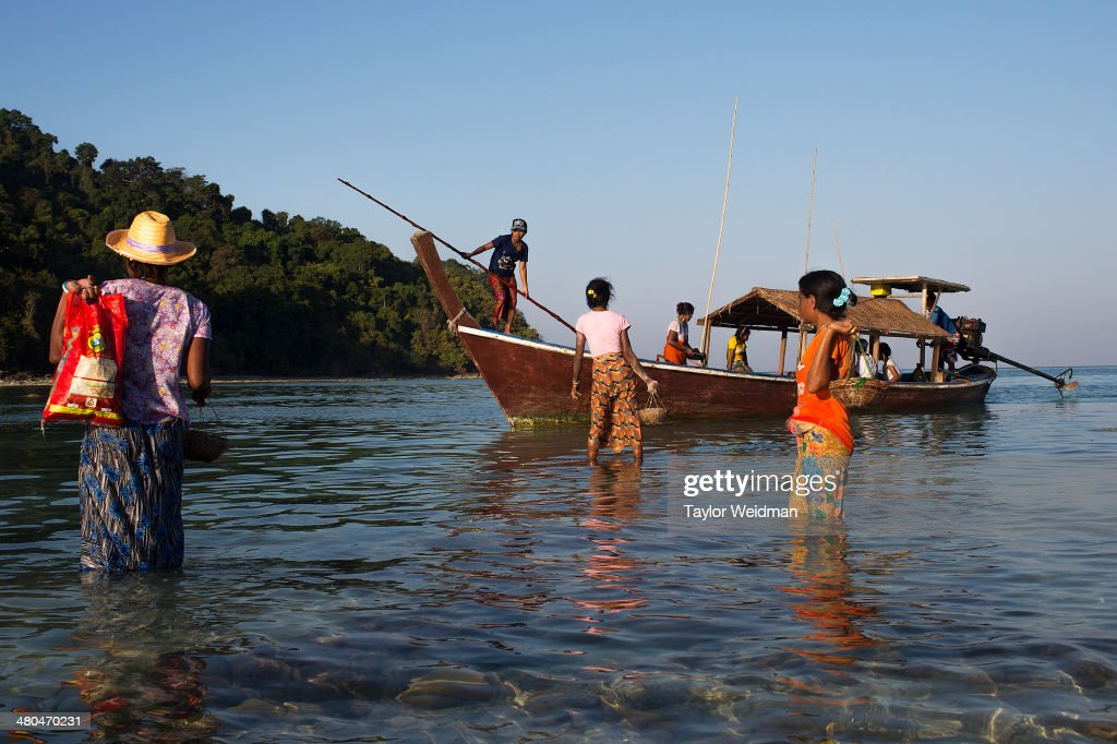 Moken women return to a long tail boat after foraging for food at a beach near their village Often called sea nomads or sea gypsies the Moken are a...