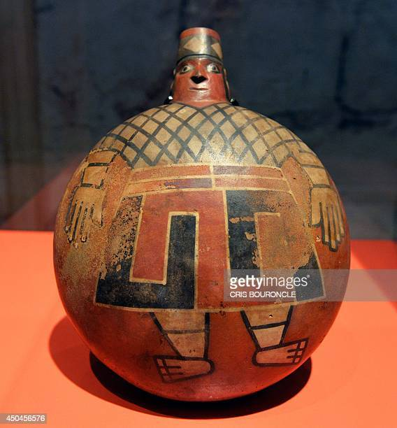 A molded and painted canteen shaped jug found part of a funeral bundle depicts a human figure wearing ear ornaments a decorated head piece and a...