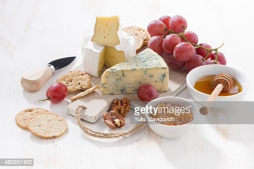 molded cheeses, fruit and snacks on a white wooden background : Stock Photo