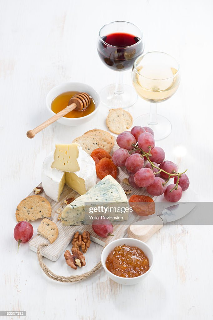 molded cheeses, fruit and snacks on a white wooden table : Stock Photo