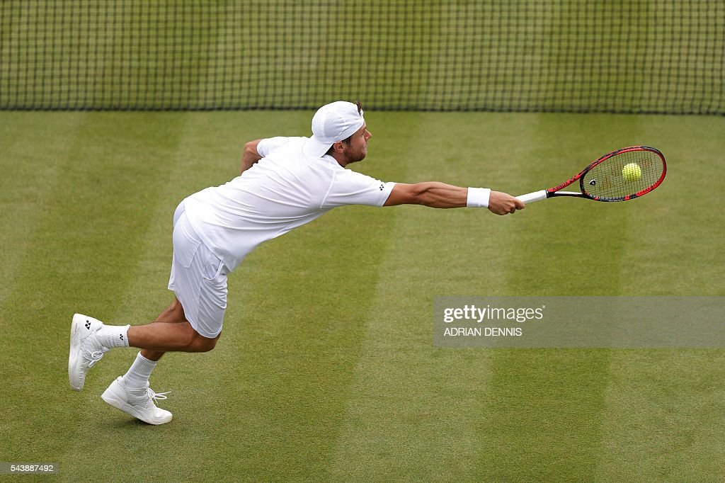 Moldova's Radu Albot returns against Australia's Bernard Tomic during their men's singles second round match on the fourth day of the 2016 Wimbledon Championships at The All England Lawn Tennis Club in Wimbledon, southwest London, on June 30, 2016. / AFP / ADRIAN