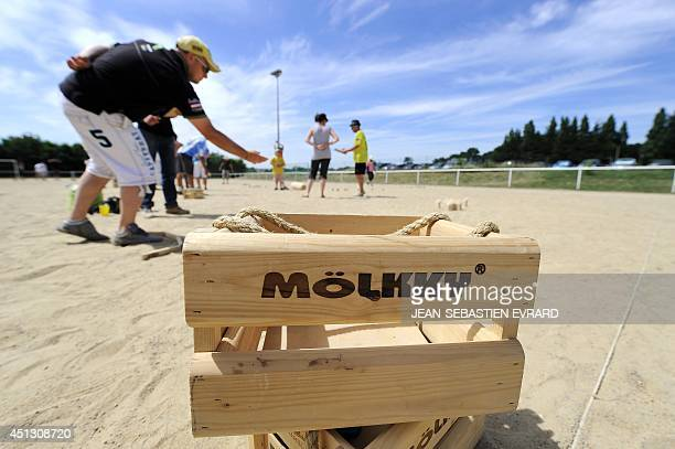 Molkky player throws a skittle while playing Molkky next to a wooden case reading 'Molkky' on June 21 2014 in L'Hermitage western France The Molkky...