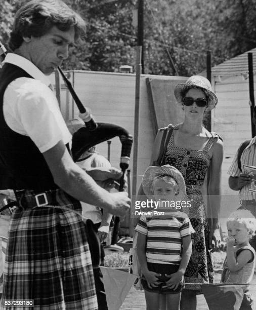 Molly Burgess and sons Beniamin right 21/2 and Mark watch a bagpipe player at the Rocky Mountain Highlands Games held in Golden Saturday The...