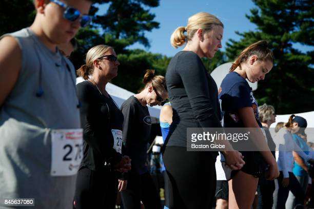 Molly Castle right and her mom April center bow their heads as a prayer is said before the start of the 16th annual Jeff Coombs Memorial 5K Walk and...