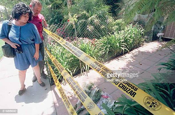 Molly McMillan and Albert Bruce from Gardena pause after placing flowers in front of the walkway in Brentwood California12 June where Nicole Brown...
