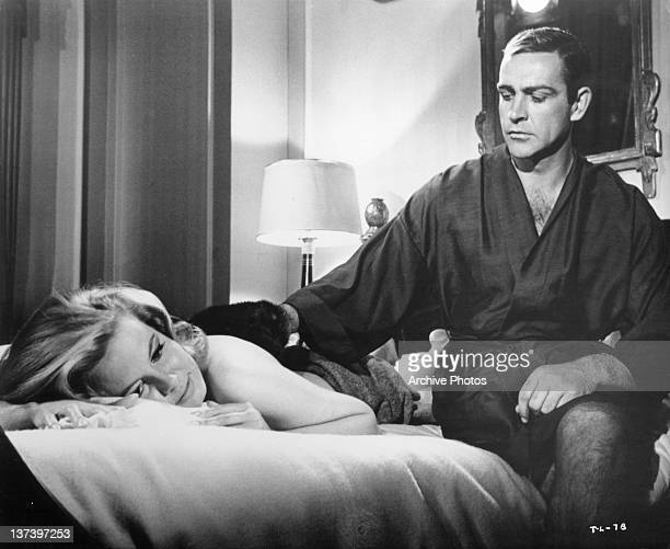 Molly Peters getting her back rubbed by Sean Connery who is wearing a robe in a scene from the film 'Thunderball' 1965