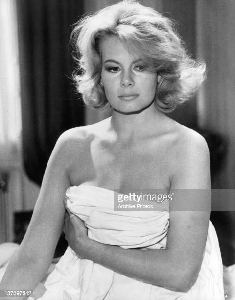 Molly Peters with a white sheet wrapped around her and holding it up with her left arm across her chest in a scene from the film 'Thunderball' 1965