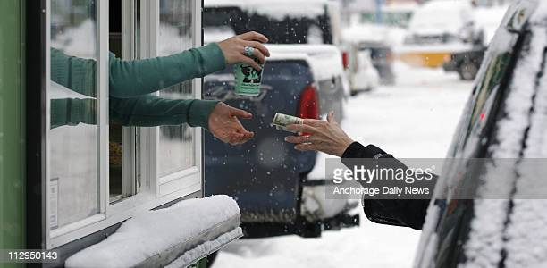 Molly Quinlan barista at Jitters driveup espresso stand hands a drink and collects payment from a motorist in Anchorage Alaska on January 23 2007