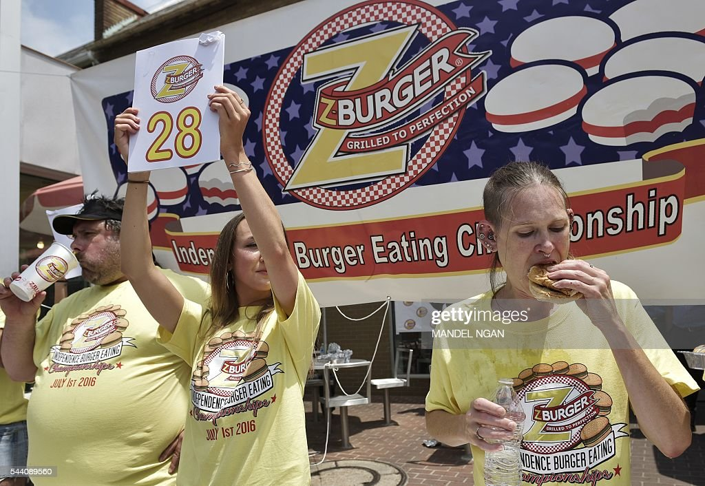 Molly Schuyler (R) finishes her 28th burger in 12 minutes to win the Zburger Independence Burger Eating Championship on July 1, 2016 in Washington, DC. / AFP / Mandel Ngan