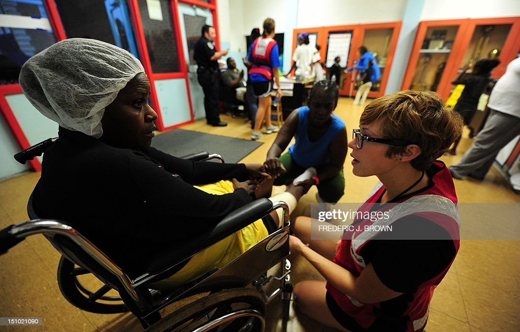 Molly Weisenburger from the Red Cross (R) tends to Lear Hill who arrived on a wheelchair seeking treatment for her injured knee at an evacuation shelter in Kentwood, northeast of New Orleans on August 30, 2012 in Louisiana, where Tropical Storm Isaac has dumped more rain onto an already saturated Gulf Coast leaving residents to seek safety from flooding. Authorities in two states along the US Gulf Coast urged residents to seek shelter amid fears the Percy Quin dam in Mississippi near the Louisiana border showed signs of damage due to the storm. AFP PHOTO / Frederic J. BROWN