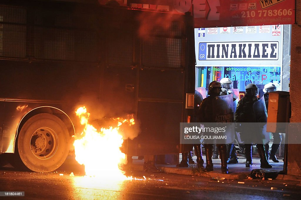 A molotov cocktail burns next to a riot police van on September 25, 2013 at the end of massive demonstration against the fatal September 18 stabbing of 34-year-old musician Pavlos Fyssas by unemployed truck driver George Roupakias. . Greek police clashed with protesters in Athens late on September 25 at the end of the march sparked by the murder of an anti-fascist musician, allegedly at the hands of a self-confessed neo-Nazi. Protesters were seen hurling petrol bombs at riot police, who responded with tear gas a few hundred meters (yards) from the headquarters of the neo-Nazi party Golden Dawn.