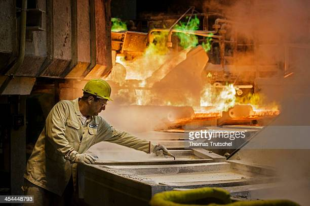 Molten copper is cast into copper anodes in the foundry of the Aurubis AG an employee is cleaning the casting ladles before they are filled with the...