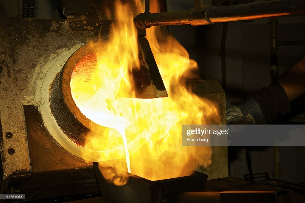 Molten gold pours from a crucible into a 400 ounce gold bar mould during the semiautomated gold bar manufacturing process at a precious metal...