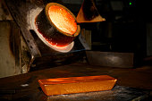 Molten gold sits in a crucible as a freshly cast 400 ounce gold bar sits on a workbench at a precious metal refinery near Mendrisio Switzerland on...
