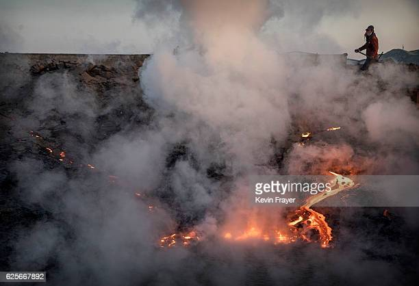 Molten iron runs down an embankment as a Chinese labourer loads coal into a furnace as he works at an unauthorized steel factory on November 4 2016...
