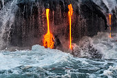 Molten lava flowing into the Pacific Ocean on Big Island, forming a lava fall along with waterfall