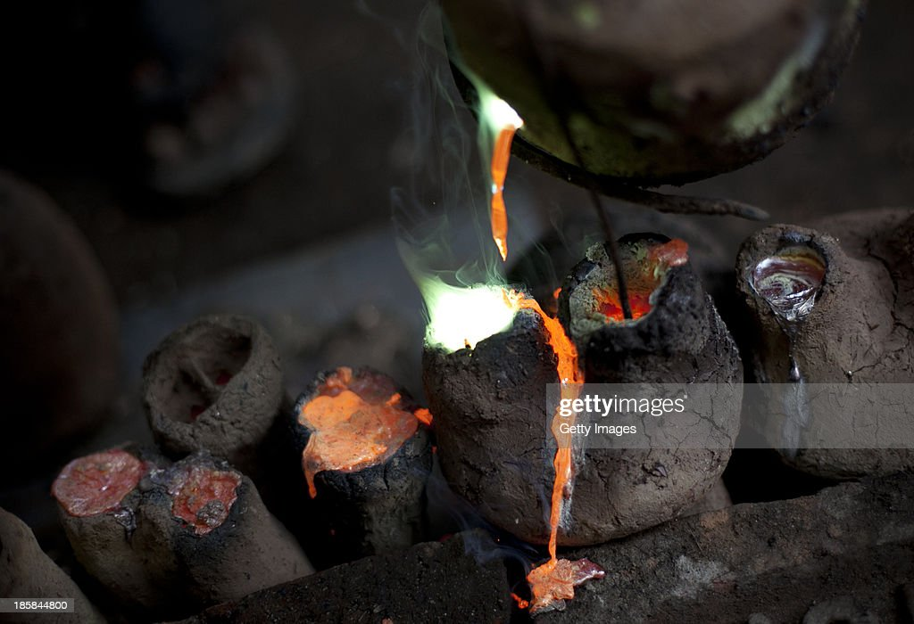 Molten metal is poured into clay sculptures at Dhamrai Metal Crafts on October 25, 2013 in Dhaka, Bangladesh. The owner of the metal crafts shop, Sukanta Banik, creates bronze sculptures in the art of 'lost wax casting.' The business has been in his family for 200 years. The pieces are first molded in wax, then encased in clay, then baked in the oven, after which metal is poured into the mold. One piece can take up to 10 months to make. The business is suffering because most of these items he creates can now be mass produced in plastic, and as a Hindu artist working in Islamic Bangladesh, the 'depiction of all humans and animals are discouraged by the majority religion.' Recently it took a year and a half to send an order overseas, when Bangladeshi customs held his work in hopes for a bribe.
