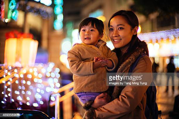 Mom a toddler girl looking at the Christmas lights