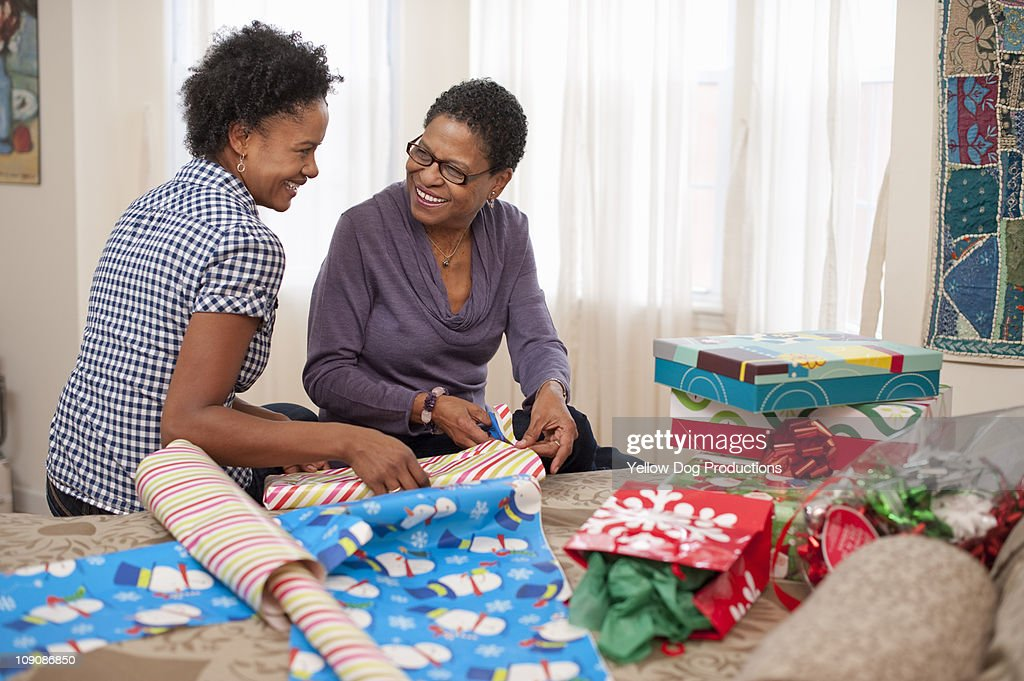 Mom and adult doughter wrapping Christmas presents : Stock Photo