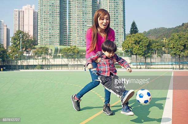Mom and baby boy playing football
