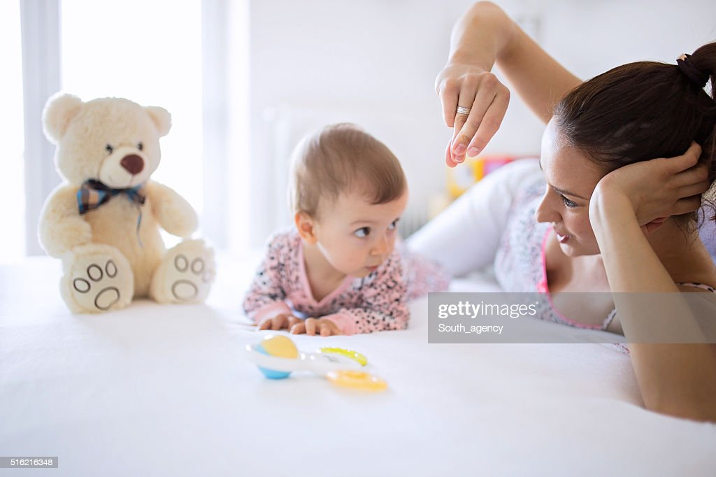 Mom and baby having fun in bedroom : Stock Photo