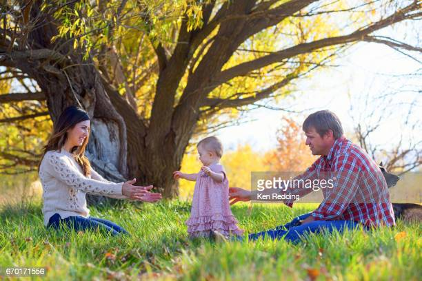 A Mom and Dad play with their baby girl in the grass