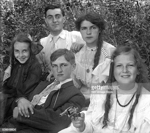 Mom and Dad pose with the children holding American flags and with a toy gun or small revolver
