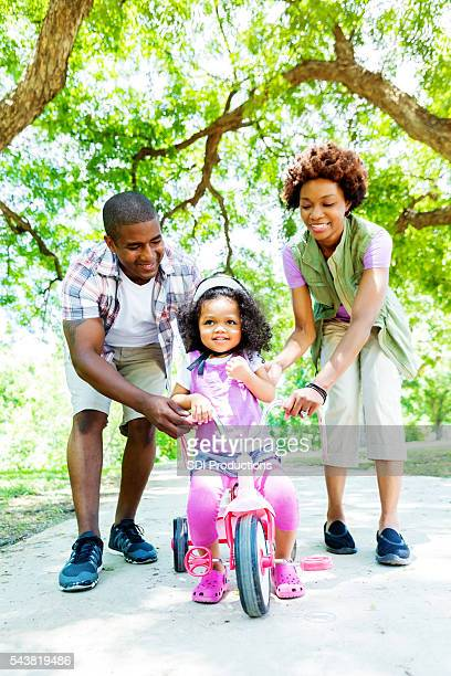 Mom and dad teach daughter to ride tricycle