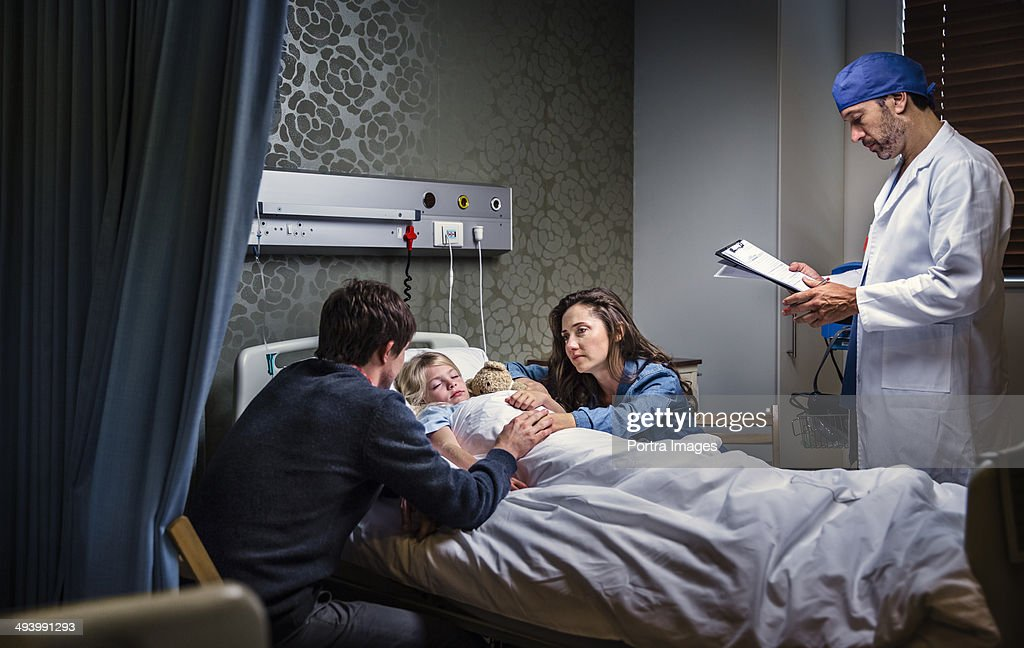 Mom and dad with a sick child in a hospital bed : Stock Photo