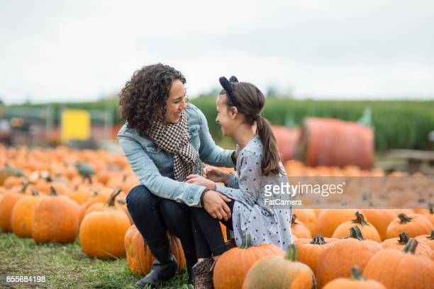 Mom and daughter at pumpkin patch farm
