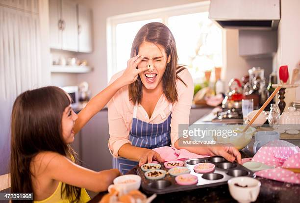 Mom and daughter having fun together in kitchen while baking