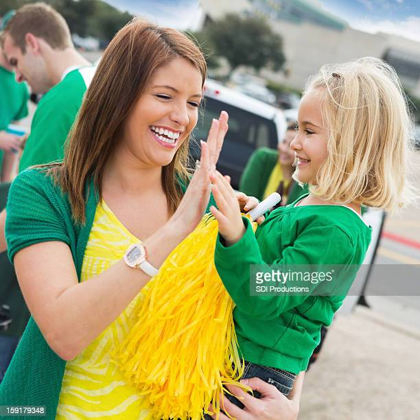 Mom and daughter high fiving during college stadium football tailgate
