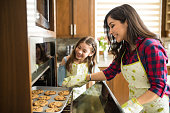 Portrait of excited mom and daughter taking freshly bakes cookies out of the oven