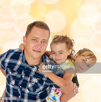 Mom and daughter look out from behind dad : Stock Photo