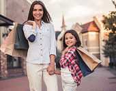 Beautiful mom and her cute little daughter are carrying shopping bags, holding hands, looking at camera and smiling while standing outdoors