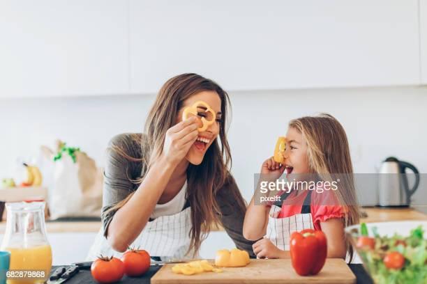 Mère et fille jouant avec des tranches de poivron