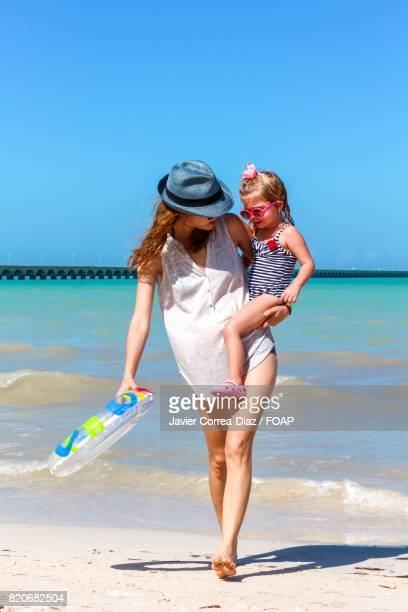 Mom and daughter walking on beach