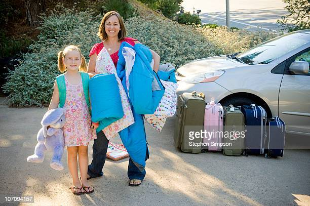 Mom and girl packing the van for a drive vacation
