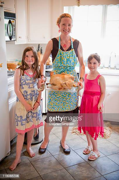 mom and girls in kitchen with turkey