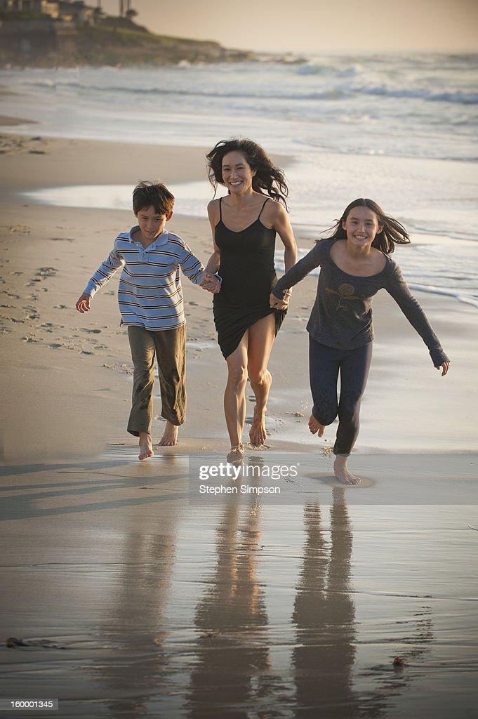 mom and her kids running on the beach : Stock Photo