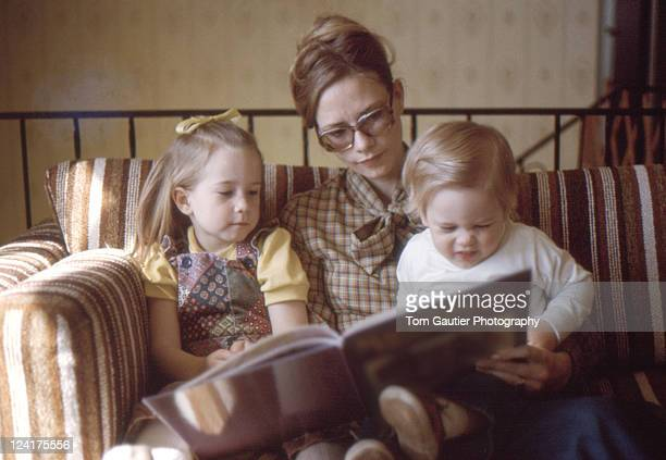 Mom and her little kids looking book