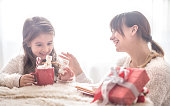Mom and her cute daughter are eating Christmas sweets in the living room on a bright background, the concept of family values and festive atmosphere