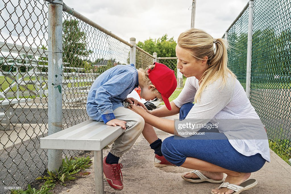Mom and son blowing on scraped knee on baseball bench. : Stock Photo