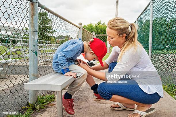 Mom and son blowing on scraped knee on baseball bench.